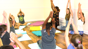 kids meditation class with big kids teaching younger kids