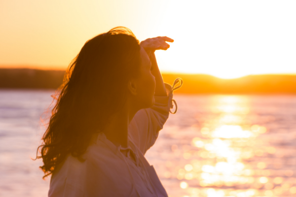 trauma release can bring inner peace (woman looking at ocean sunrise)